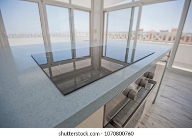 Interior design decor showing modern kitchen and cooker appliance in luxury penthouse apartment showroom with panoramic patio windows