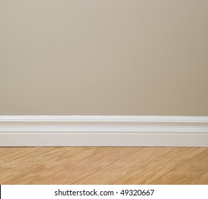 Interior design detail. Beige wall, clean white baseboard molding and wooden floor.