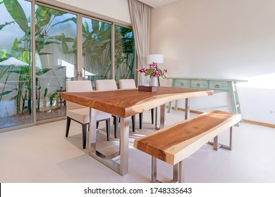 Interior design of dining area in luxury villa, apartment feature wooden dining table, bench and white dining chair