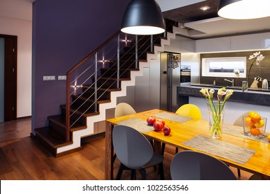 Interior design - dining table and chairs in a modern kitchen with staircase