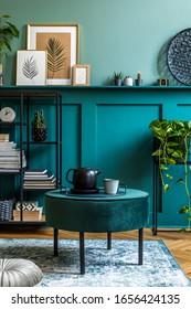 Interior design of living room with green pouf, tea pot, modern shelf, plants, books, accessories, mock up poster frames, rattan decoration and stylish carpet. Home staging. Wood panelling. Template.