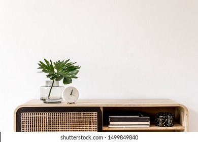 Interior design of living room at scandinavian apartment with stylish commode, tropical leaf in vase, books, white clock and elegant accessories. Modern home decor. Template. Copy space. White walls.