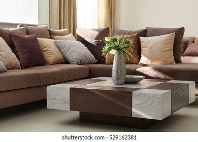 Interior Design. Luxurious living room with a coffee table made of wood and lilies in a vase.
