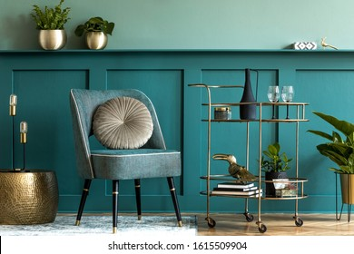 Interior design of luxury living room with stylish armchair, gold liquor cabinet, a lot of plants and elegant personal accessories. Green wall panelling with shelf. Modern home decor. Template.  - Shutterstock ID 1615509904
