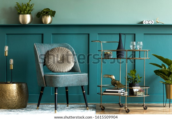 Interior design of luxury living room with stylish armchair, gold liquor cabinet, a lot of plants and elegant personal accessories. Green wall panelling with shelf. Modern home decor. Template.