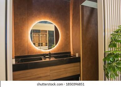 Inneneinrichtung eines luxuriösen Show-Home-Badezimmers mit zwei Waschbecken und einem runden Spiegel