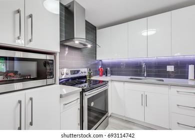 Interior design of modern kitchen with stainless steel appliances, back splash, fruit basket.