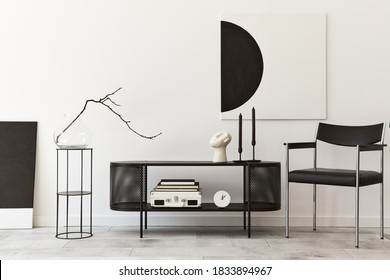 Interior design of modern living room with black stylish commode, chair, mock up art paintings, lamp, book, candlestick, decorations and elegant accessories in home decor. Template.