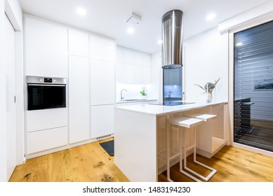 Interior design new modern white kitchen with kitchen appliances. Luxury residential kitchen with sink, stove, hob and white wooden cupboards and hard wood floor.