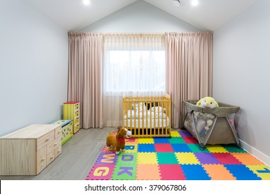 Interior design of a nursery room with a crib and toys.