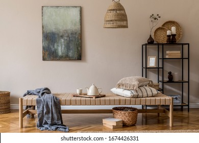 Interior design of oriental living room with modern chaise longue, pillows, plaid, rattan decoration, modern shelf, elegant personal accessories and mock up paintings on the beige wall.