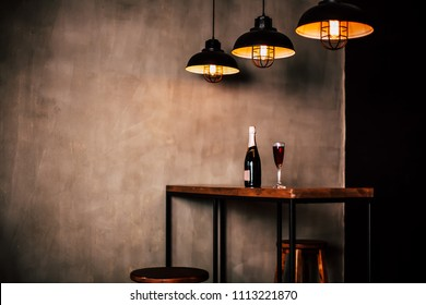 Interior design of restaurant or cafe. Side Photo of wooden table with bottle champagne or wine and glass with drink on it, three modern lamps above table