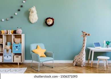 Interior design of scandinavian childroom with wooden cabinet, mint armchair, white desk, a lot of plush and wooden toys. Eucalyptus color of background walls. Plush animal head on the wall. Template