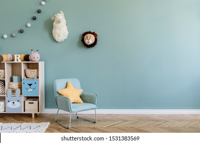 Interior design of scandinavian childroom with wooden cabinet, mint armchair, a lot of plush and wooden toys. Eucalyptus color of background walls. Plush animal head on the wall. Template Copy space