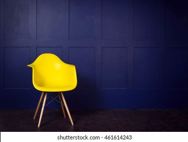 Interior design scene with a modern yellow chair on blue wall, copy space in the wall