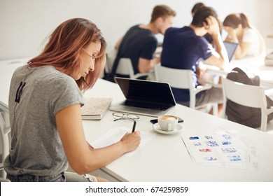 Interior design student filling out forms working in a campus or a bright coworking studio with people on background. Education concept.