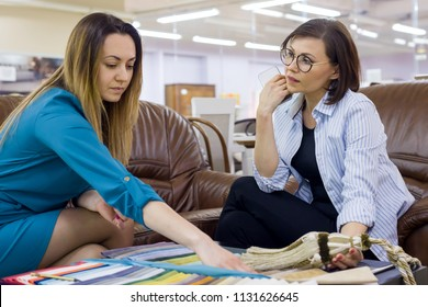 Interior designer and adult woman matching color samples of fabrics for curtains, home textile store, decor