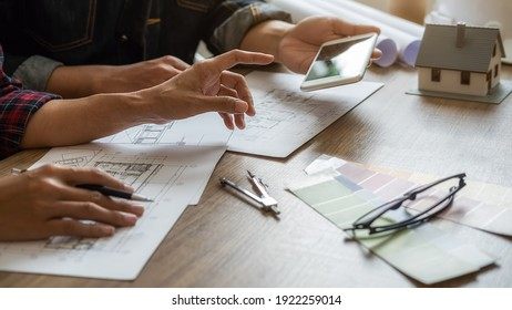 Interior designer and Architect choosing color in color swatch samples chart for house coloring selection in office with blueprint. Construction concept.