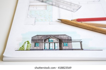 Amazing Interior Designer Or Architect Hand Working With Blueprints Equipment  Objects And Color Image Of Drawn House