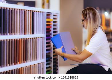 Interior designer, decorator, choosing cabinet panel and countertop material in showroom