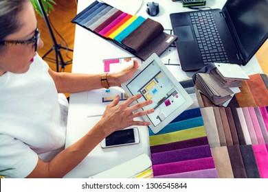 Interior designer, decorator, choosing  material samples in studio