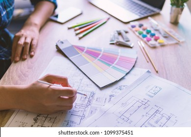 Interior designer designs make color on blueprint of house for present with customer.  engineering design at workplace concept.