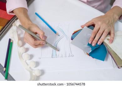 Interior designer draws with pencil curtain model in the interior