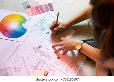 Interior designer draws plan with pencil