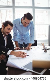 Interior designer explaining blueprint to male coworker in office