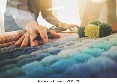 Interior designer hand choosing carpet sample with blank new modern computer laptop and pro digital tablet with material board on wooden desk as concept