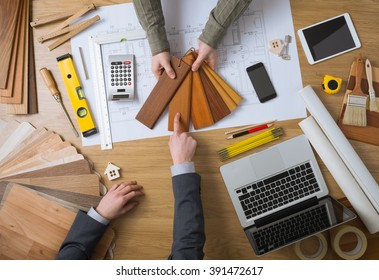 Interior designer showing wood swatches to his customer, laptop, tools and house projects on desktop top view