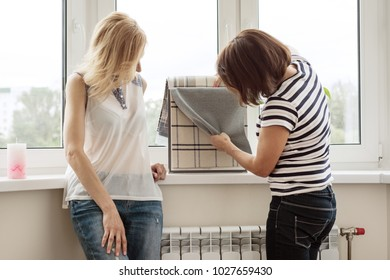 Interior designer shows samples of fabrics and accessories for curtains in the new house. Picture in the window background