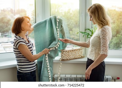 Interior designer shows samples of fabrics and accessories for curtains in the new house. Picture in the window background.