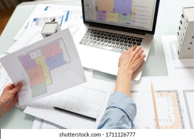 Interior designer working with an apartment plans in a studio, with blueprints and laptop on a table. Architectural desigh bureau working concept
