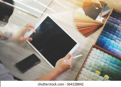 interior designer working with digital tablet and new modern computer laptop with sample material on wooden desk as concept