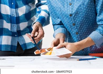 Innenarchitekten diskutieren Farbmuster für Design-Projekte. Nahaufnahme der Hand mit Bleistift, der auf die Farbpalette zeigt. Professionelles Gebäude, Dekoration und Renovierung. Teamwork und Kreativität