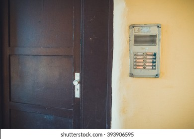 Interior Detail of Closed Apartment Door Next to Old Security Intercom System Mounted on Old Grungy Yellow Painted Wall
