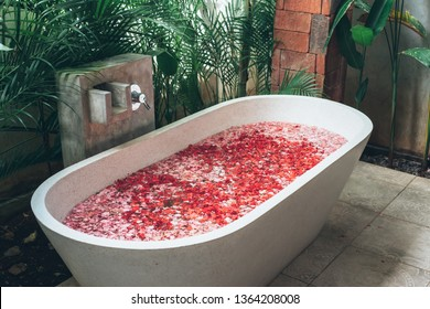 Interior details with bathtub with flower petals. Organic spa relaxation in luxury Bali outdoor bath.