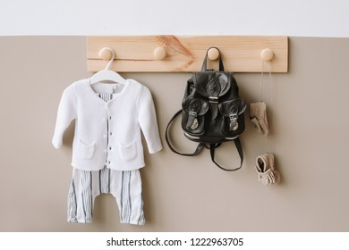 Interior details of children's room on light background. Decorative wooden hanger with bag on white and brown wall as detail of kid interior. Children's room with light wall, interior details