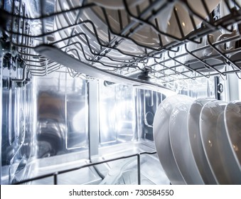 Interior of dishwasher machine with clean dishes after washing
