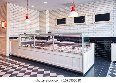 Interior display showcase of a delicatessen shop with cheese, sausages and dairy products