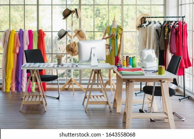 interior of dressmaker shop with dressmaking working desk and hanging rack with dress