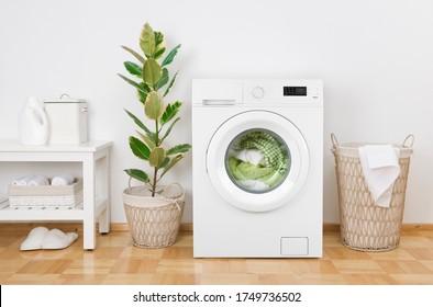 Inneneinrichtung des eleganten Wäschesaals mit Waschmaschine und Korb