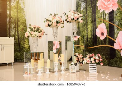 Interior elegant luxury wedding decoration photo zone. Photo booth with flowers in glass vases, lanterns, candles, stands from mirror.