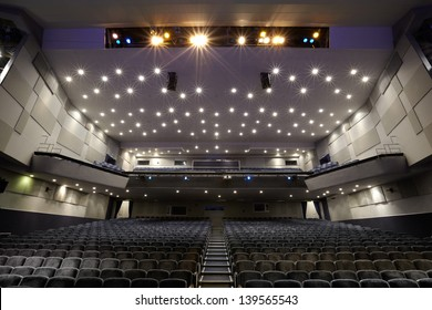 Interior of empty cinema auditorium with lines of chairs.