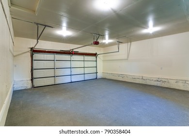 Interior of an empty clean garage with closed door in a house.