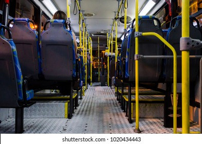 Interior of an empty collective bus at night seen from the bottom chairs