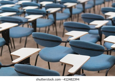 Interior of empty conference hall with blue velvet chairs with small desks for writing notes.