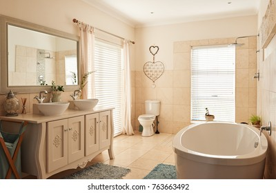 Interior of an empty country style residential bathroom with double basins, a toilet and bathtub