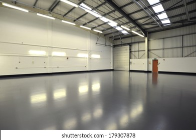 interior of empty and new warehouse with doors, grey newly painted floor